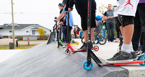 Kids with scooters are lined up at the top of a ramp at a skatepark.