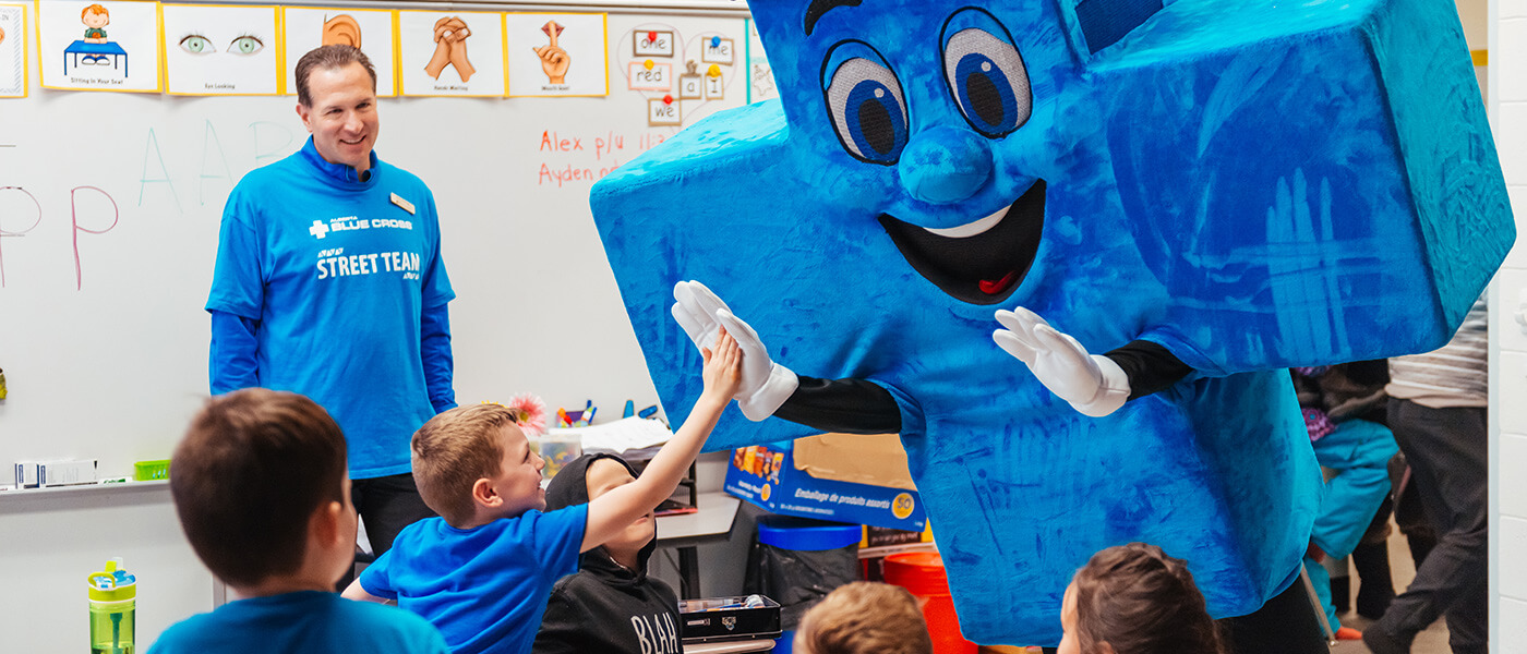 Alberta Blue Cross mascot, Big Blue, is high-fiving children in their classroom.